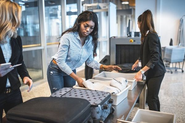 Airport-officials-check-a-passenger's-luggage
