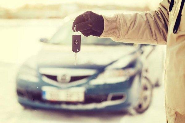 Hand-holding-car-key-over-a-car