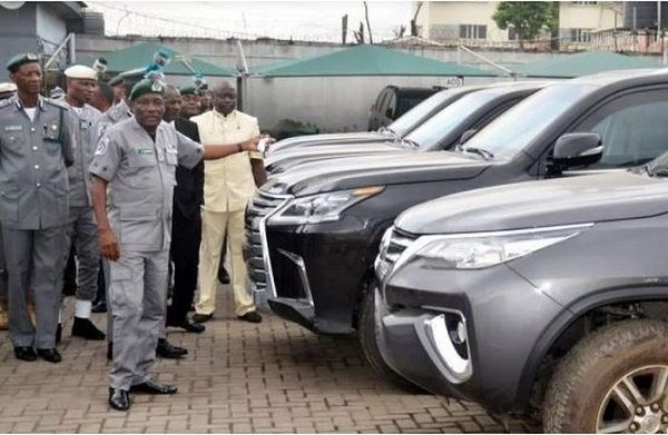 Customs-officers-beside-impounded-cars
