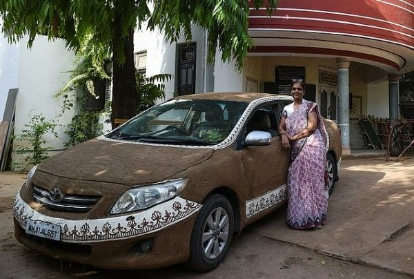 Indian-woman-poses-with-her-Toyota-Corolla-plastered-with-cow-dung