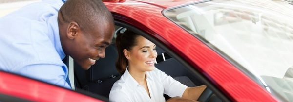 african-salesman-introduces-a-female-buyer-to-car-features