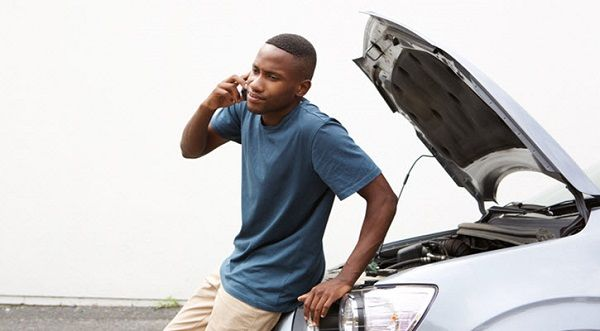 man-stands-by-stalled-car