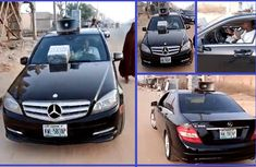 Nigerian man selling local herbs with Mercedes Benz C300