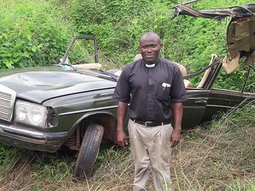 A clergyman survives deadly crash, posing beside the damaged vehicle