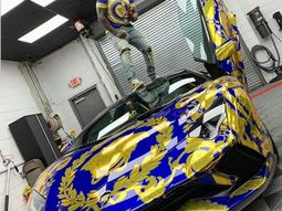 50 Cent poses with his Versace-wrapped Lamborghini Aventador
