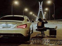 If you've got it... Mayorkun sits and drinks wine beside his Benz CLA250 AMG on Lekki-Ikoyi Link bridge